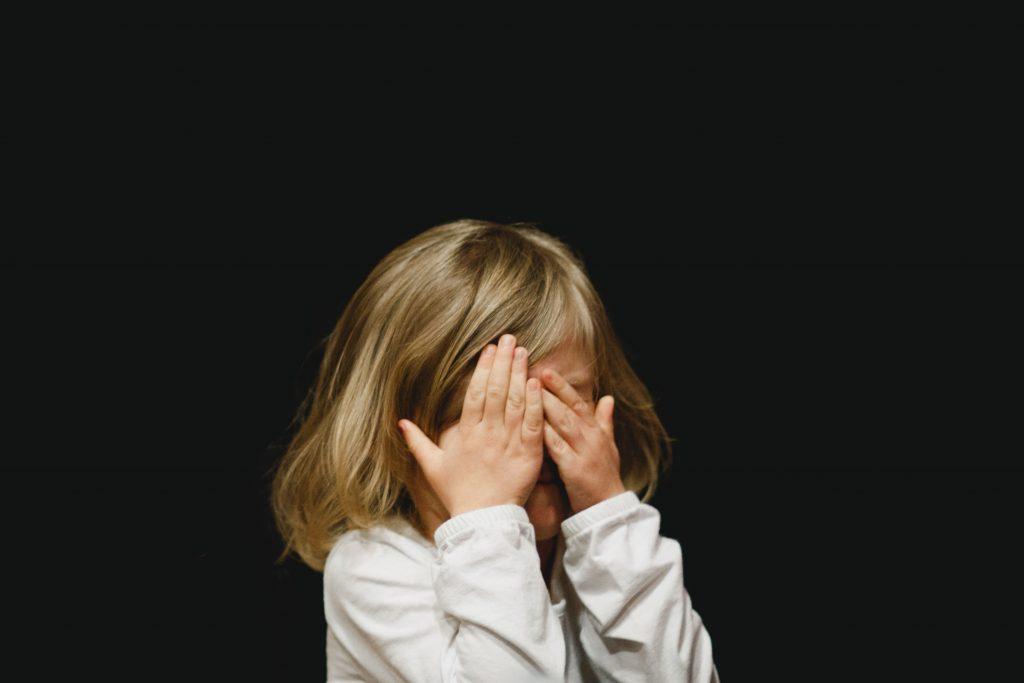 bambina con le mani sul viso