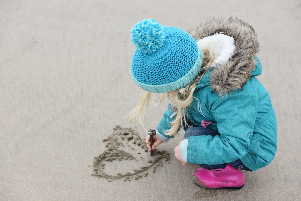 una bambina disegna un cuore sulla sabbia