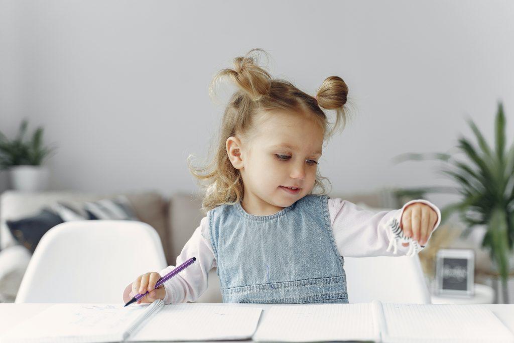 una bambina gioca e scrive