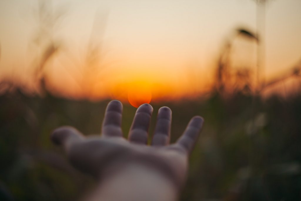 mano tesa verso un tramonto