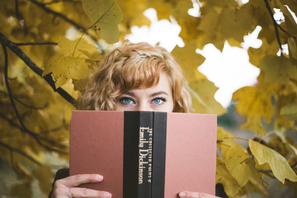 ragazza dagli occhi blu tieni un mano un libro tra gli alberi autunnali